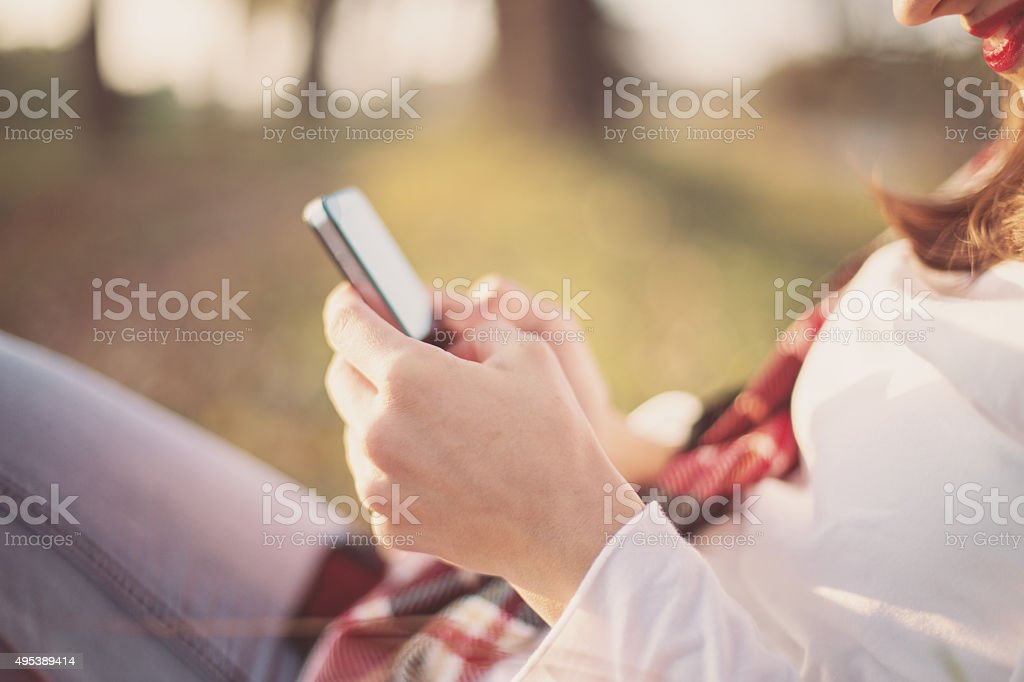 Happy woman enjoying  autumn and using smart phone stock photo