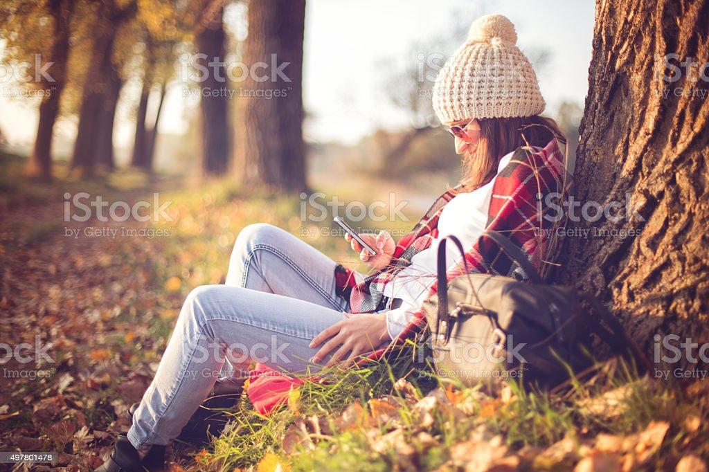 Happy woman enjoying  autumn and using smart phone stock photo