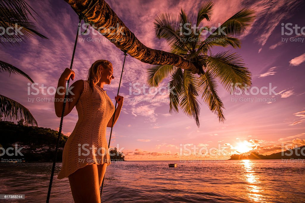 Happy woman enjoying in breathtaking sunset on the beach. stock photo