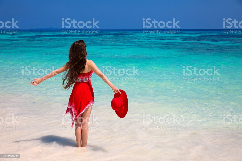 Happy woman enjoying on exotic beach in summer tropical blue stock photo