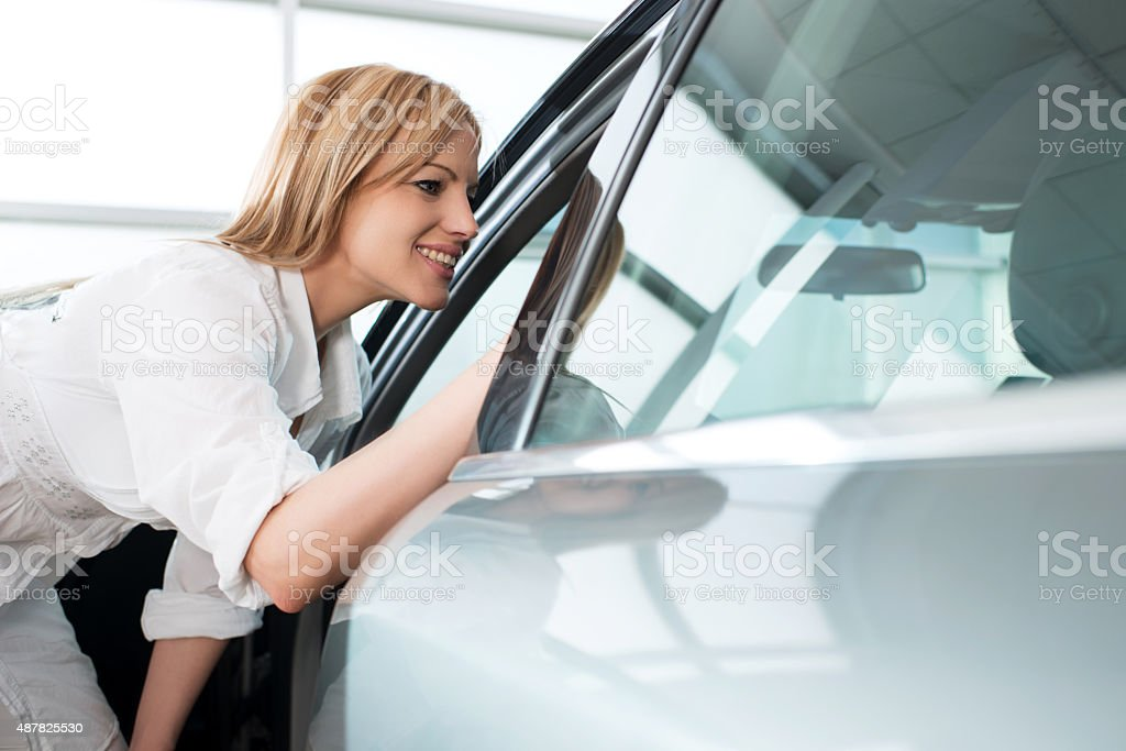 Happy woman examining a car in a showroom. stock photo