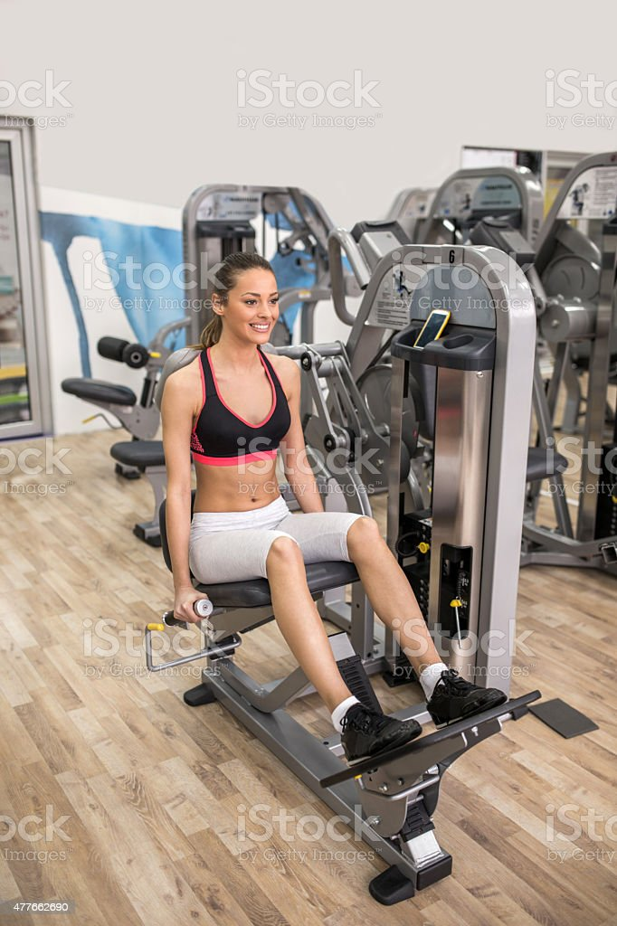 Happy woman exercising on back extension machine at gym. stock photo
