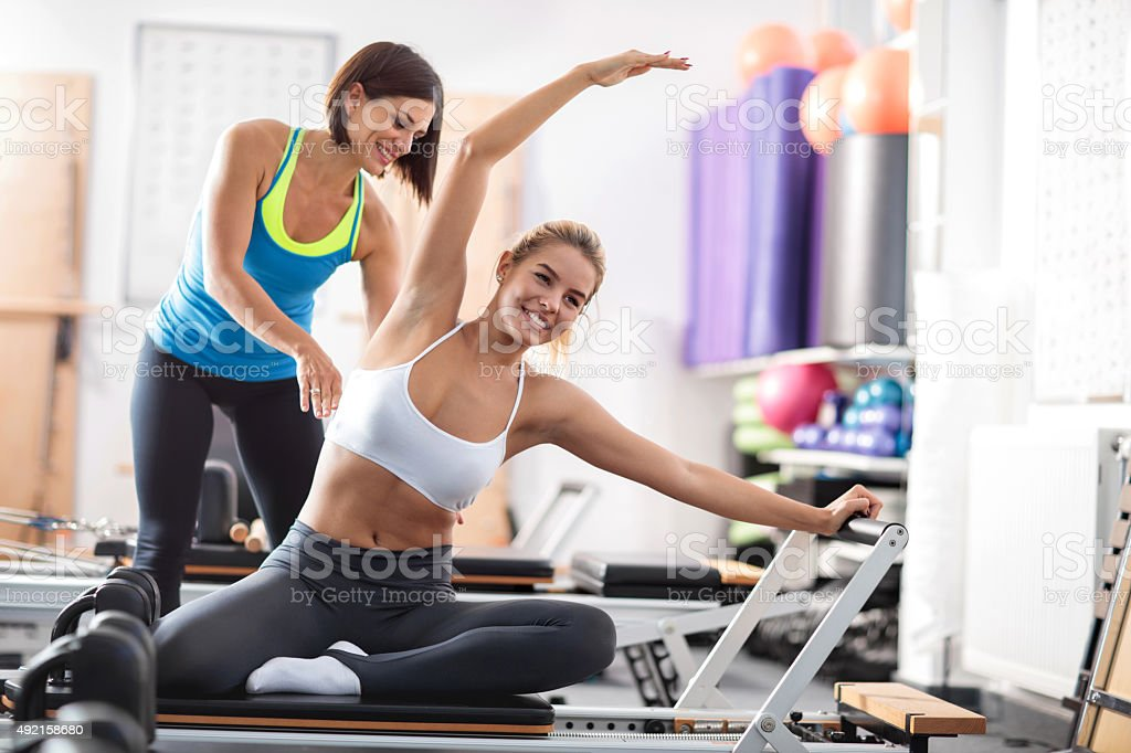 Happy woman exercising Pilates with a help of personal instructor. stock photo