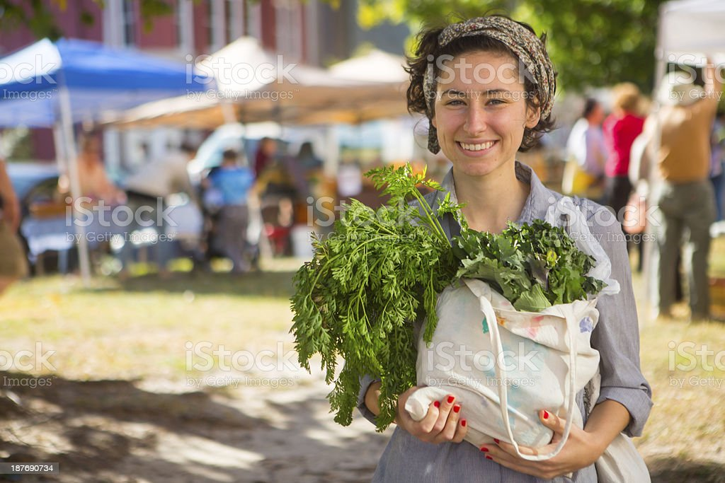 Happy woman exiting farmers market with bag of greens royalty-free stock photo