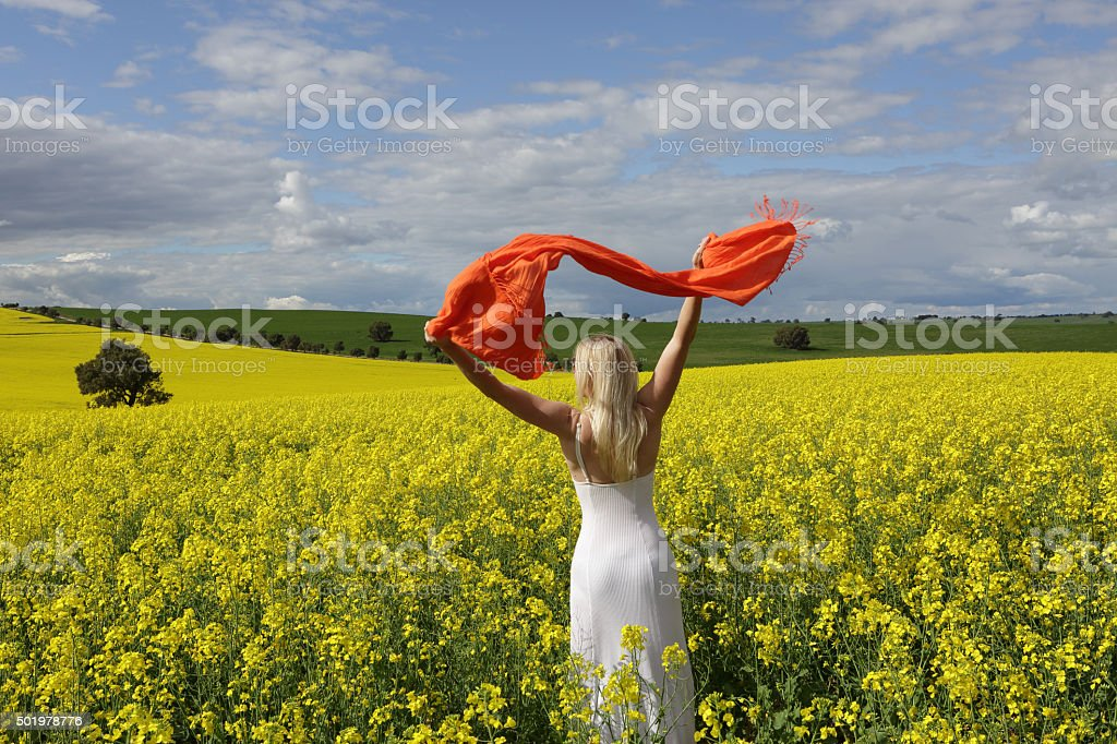 Happy woman flailing scarf in field of flowering canola spring stock photo