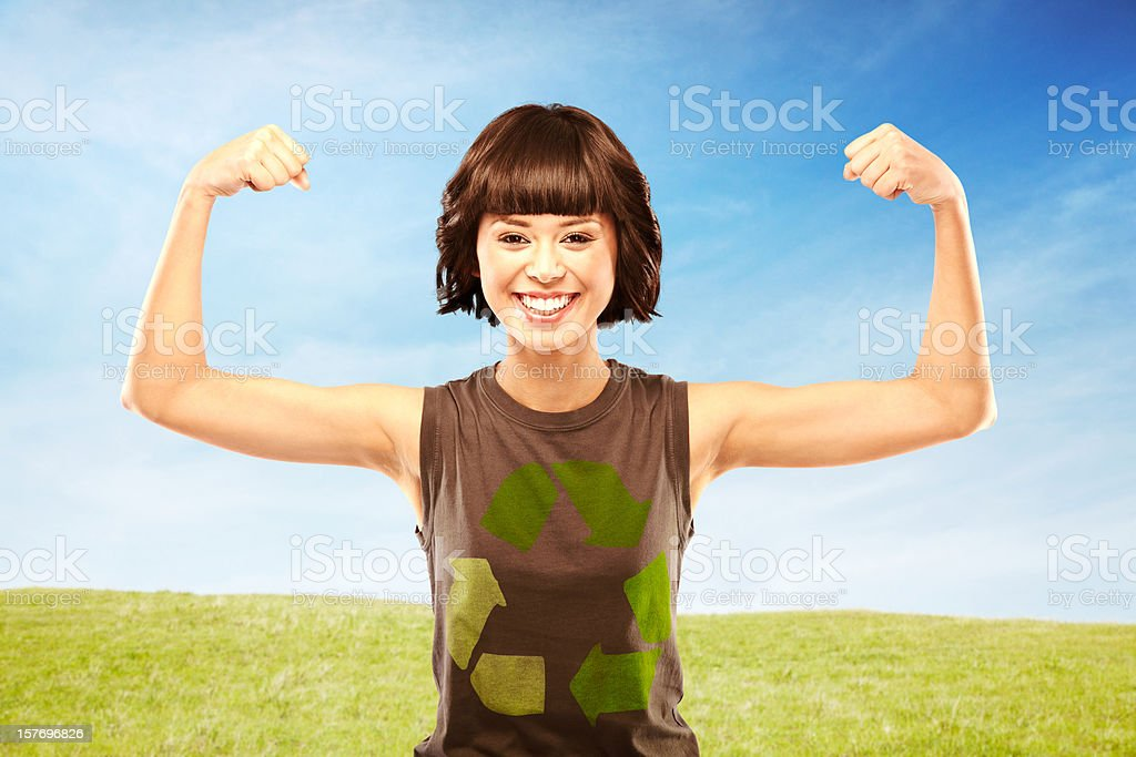 Happy woman flexing muscles wearing a recycling t-shirt royalty-free stock photo