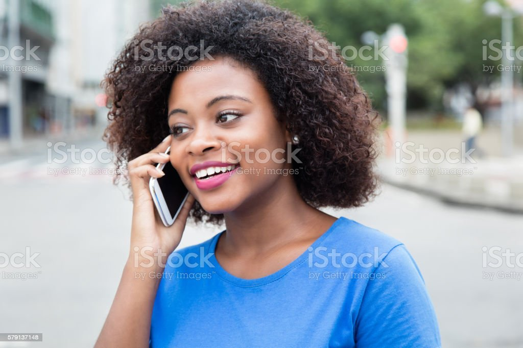Happy woman from Africa at phone stock photo