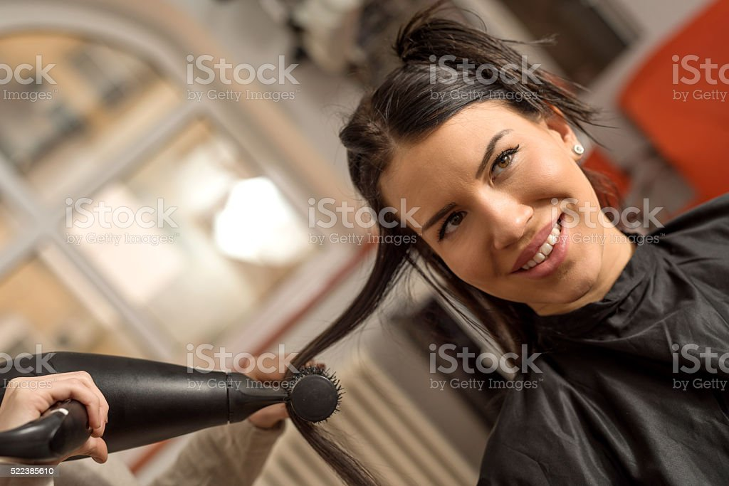 Happy woman getting her hair dried at hair salon. stock photo