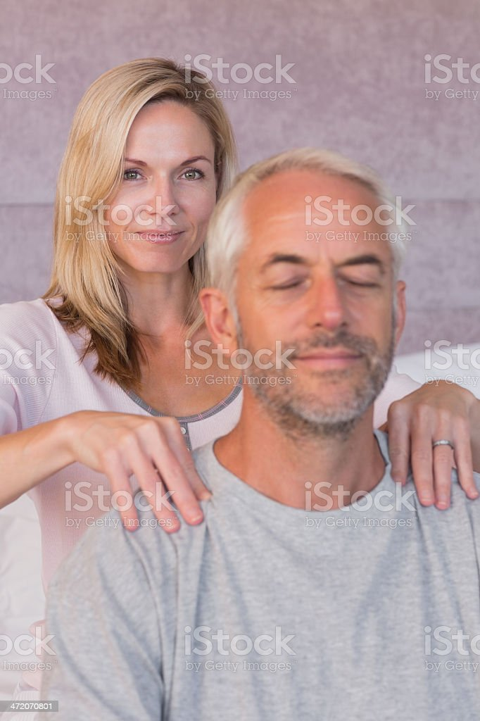Happy woman giving massage to her smiling husband royalty-free stock photo