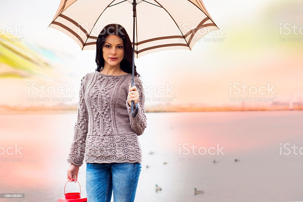 happy woman goes with an umbrella on the bridge stock photo