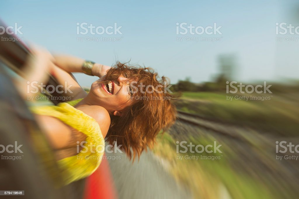 Happy Woman Hanging from Car Window stock photo