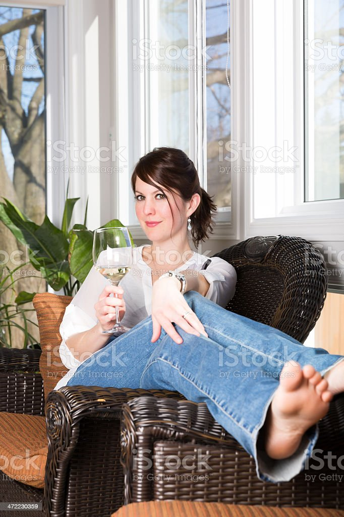 Happy Woman Having a Glass of Wine in Sunroom royalty-free stock photo