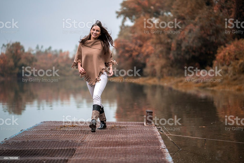 Happy woman having fun on a pier during autumn day. stock photo