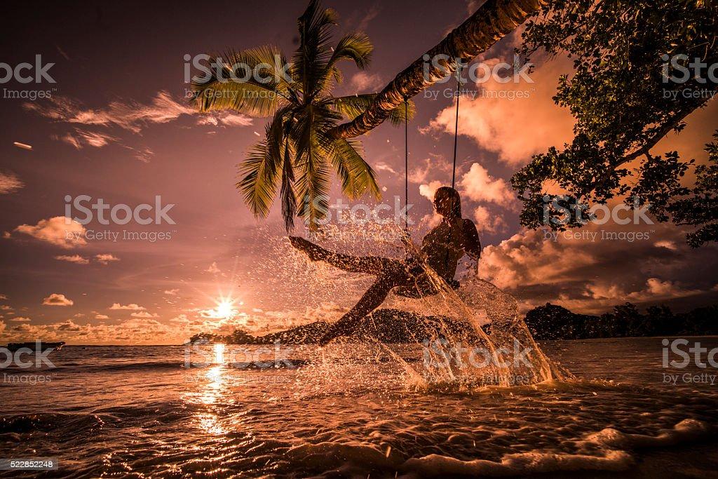 Happy woman having fun on a swing above the sea. stock photo