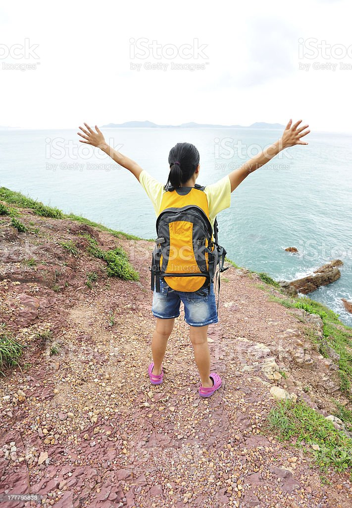 happy woman hiker stand at extrusive rock seaside stock photo