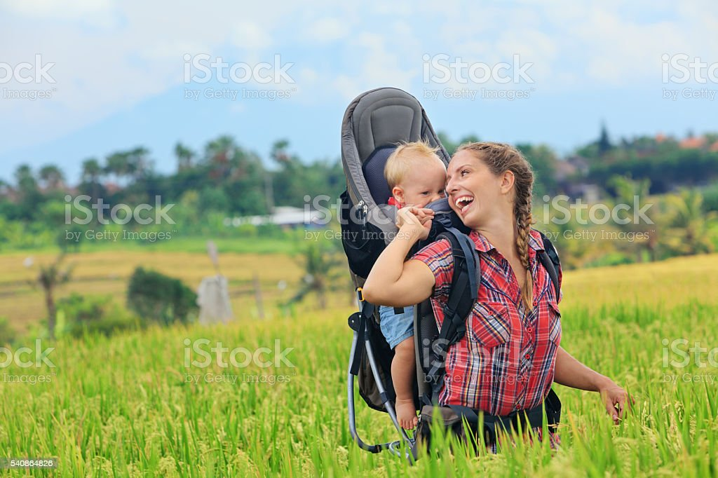 Happy woman hold child in backpack baby carrier stock photo