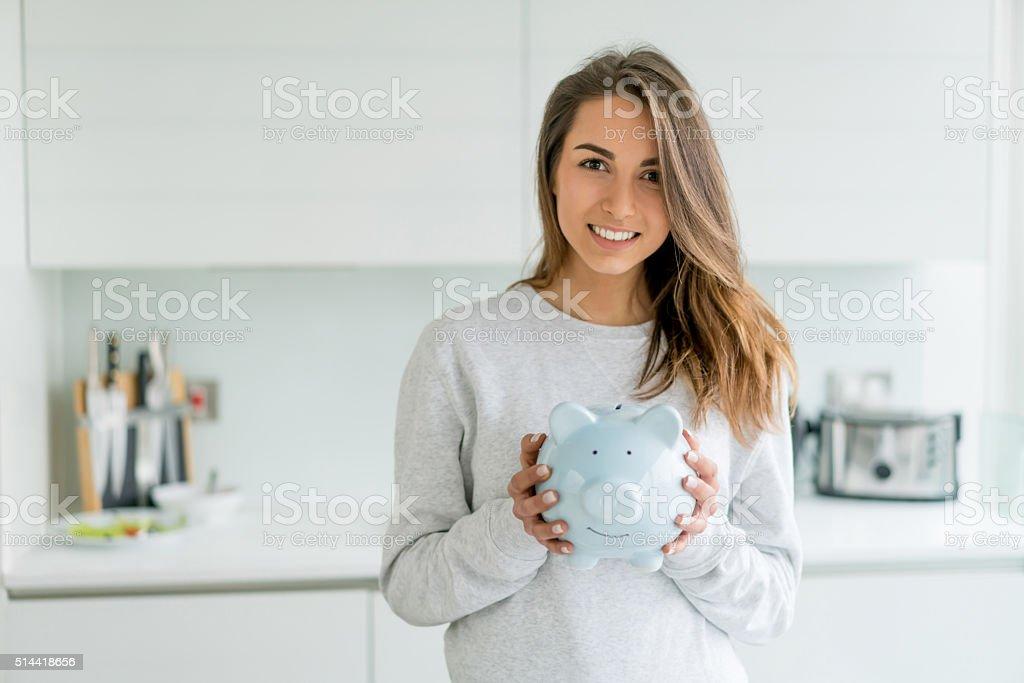 Happy woman holding a piggybank stock photo