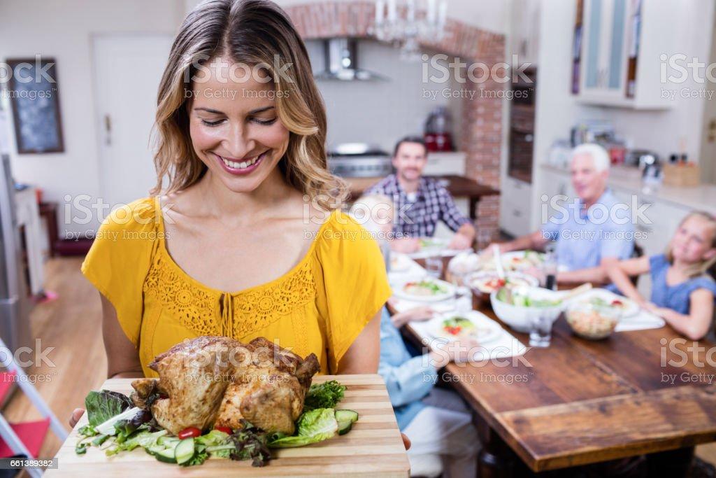 Happy woman holding a tray of roasted turkey stock photo