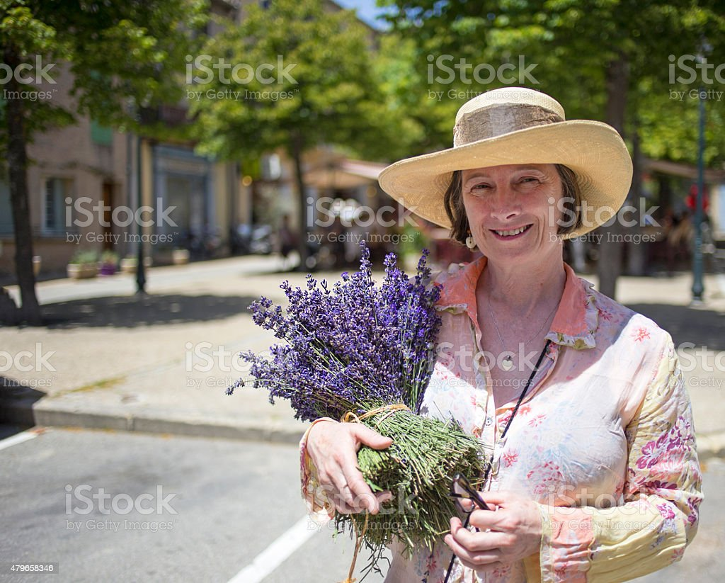 Happy woman holding bunches of fresh lavender stock photo