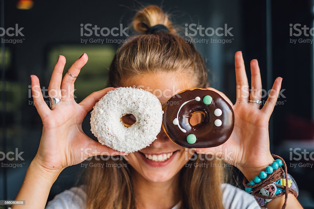 Happy woman holding donuts stock photo