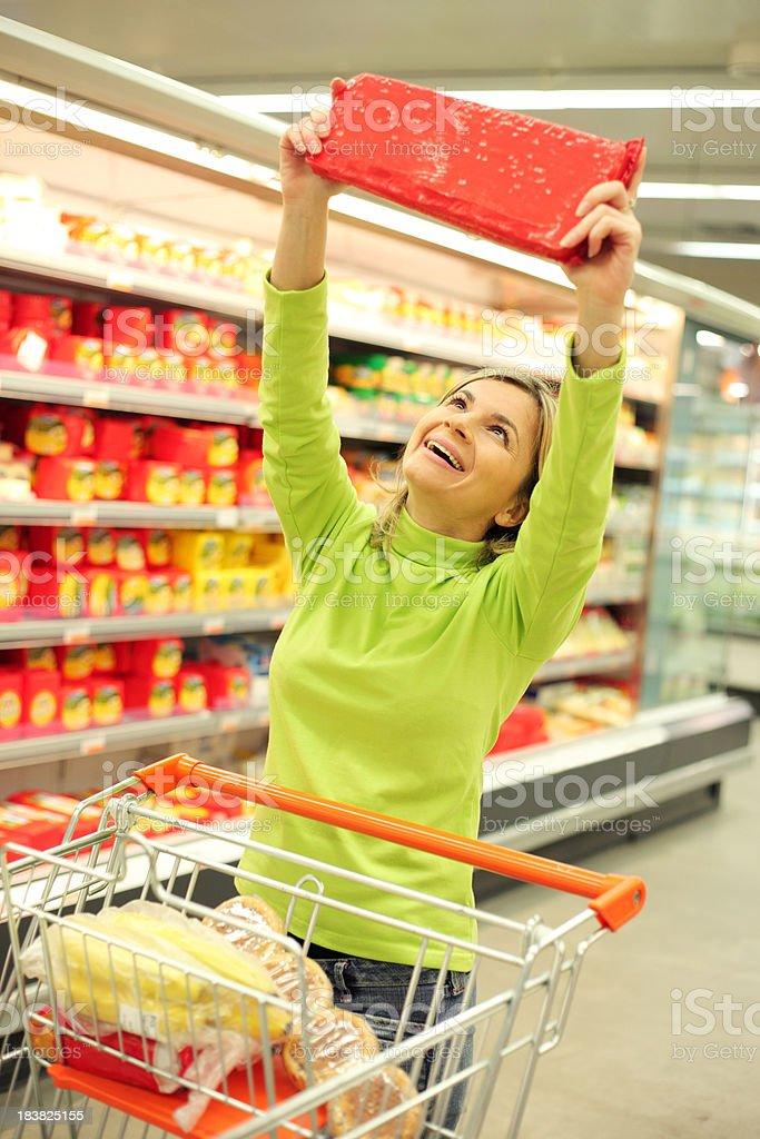 Happy woman holding foodstuffs at the big supermarket. royalty-free stock photo