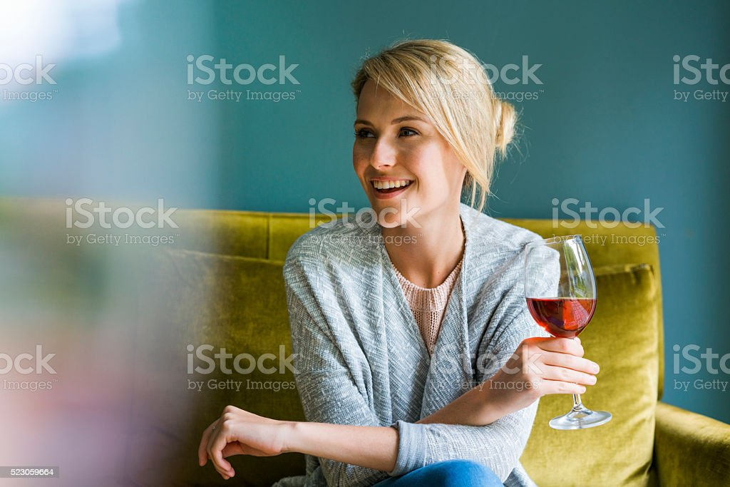 Happy woman holding glass of red wine on sofa stock photo