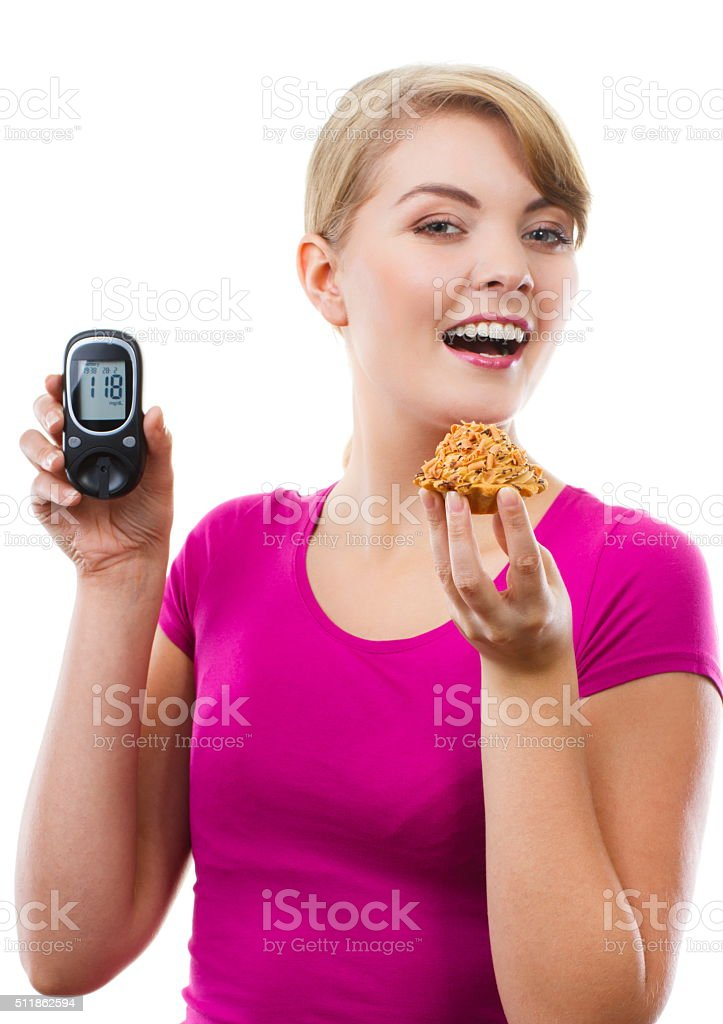 Happy woman holding glucometer and eating fresh cupcake stock photo