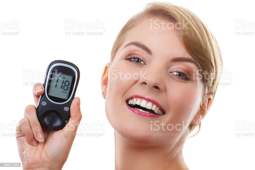 Happy woman holding glucometer, measuring sugar level, concept of diabetes stock photo