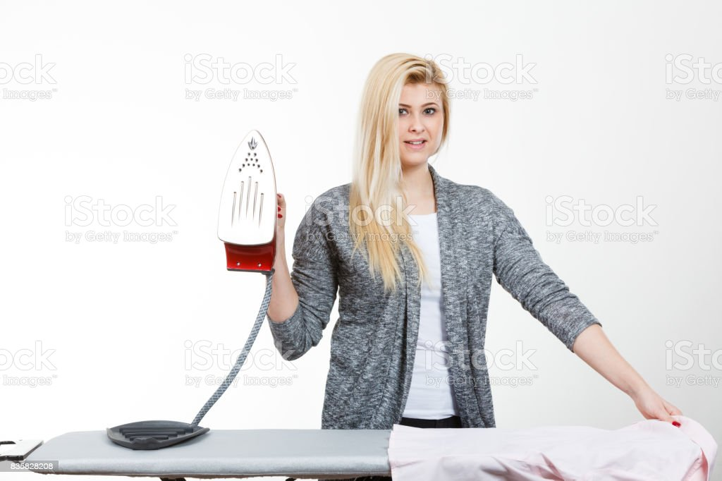 Happy woman holding iron about to do ironing stock photo