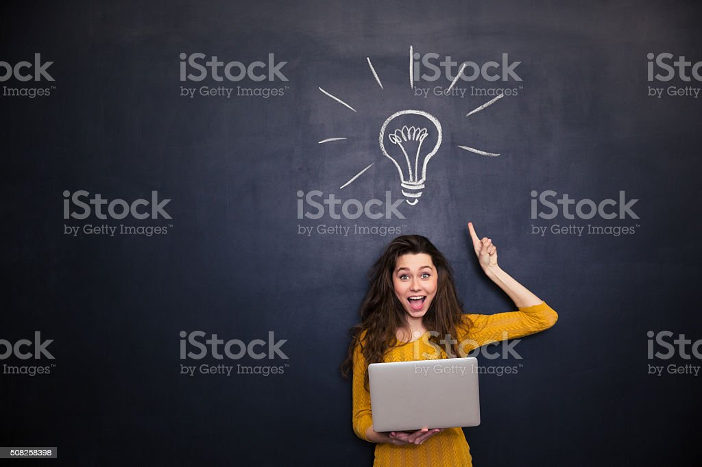 Happy woman holding laptop and having idea over blackboard background stock photo