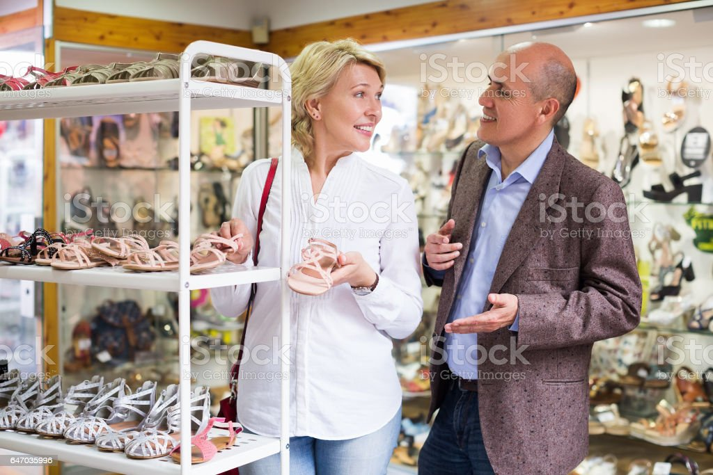 Happy woman holding shoes stock photo