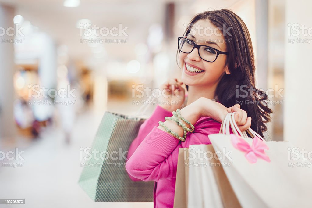 Happy woman holding shopping bags in a shopping mall stock photo