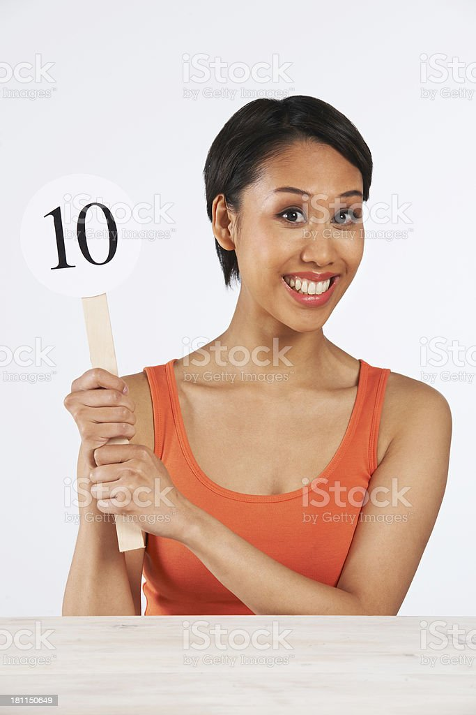 Happy Woman Holding Up Scorecard Giving Mark Out Of Ten stock photo