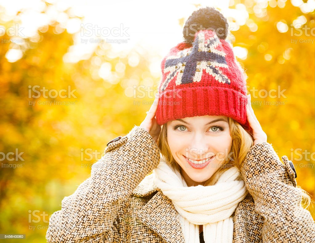 Happy Woman in Beanie Hat on Autumn Background stock photo