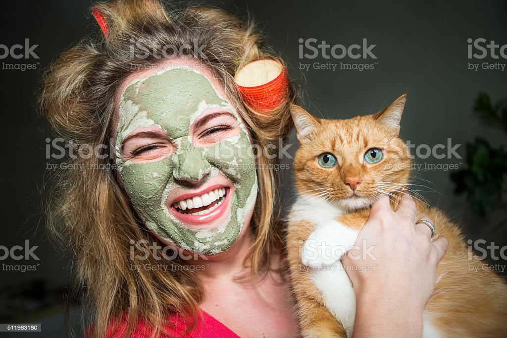 Happy woman in curlers and a mask on his face stock photo