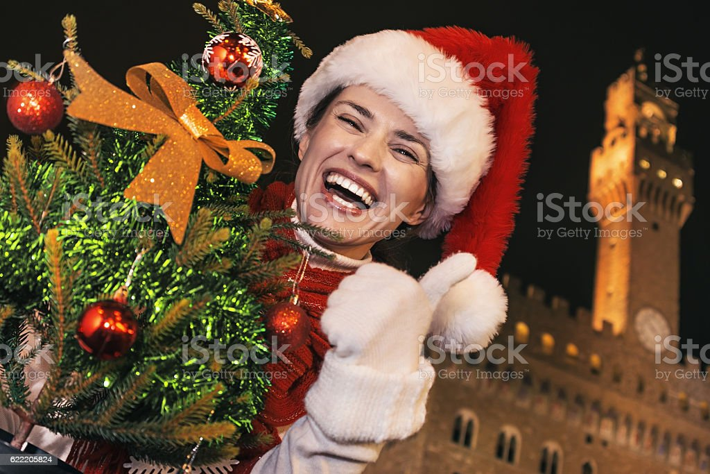 happy woman in Florence with Christmas tree showing thumbs up stock photo
