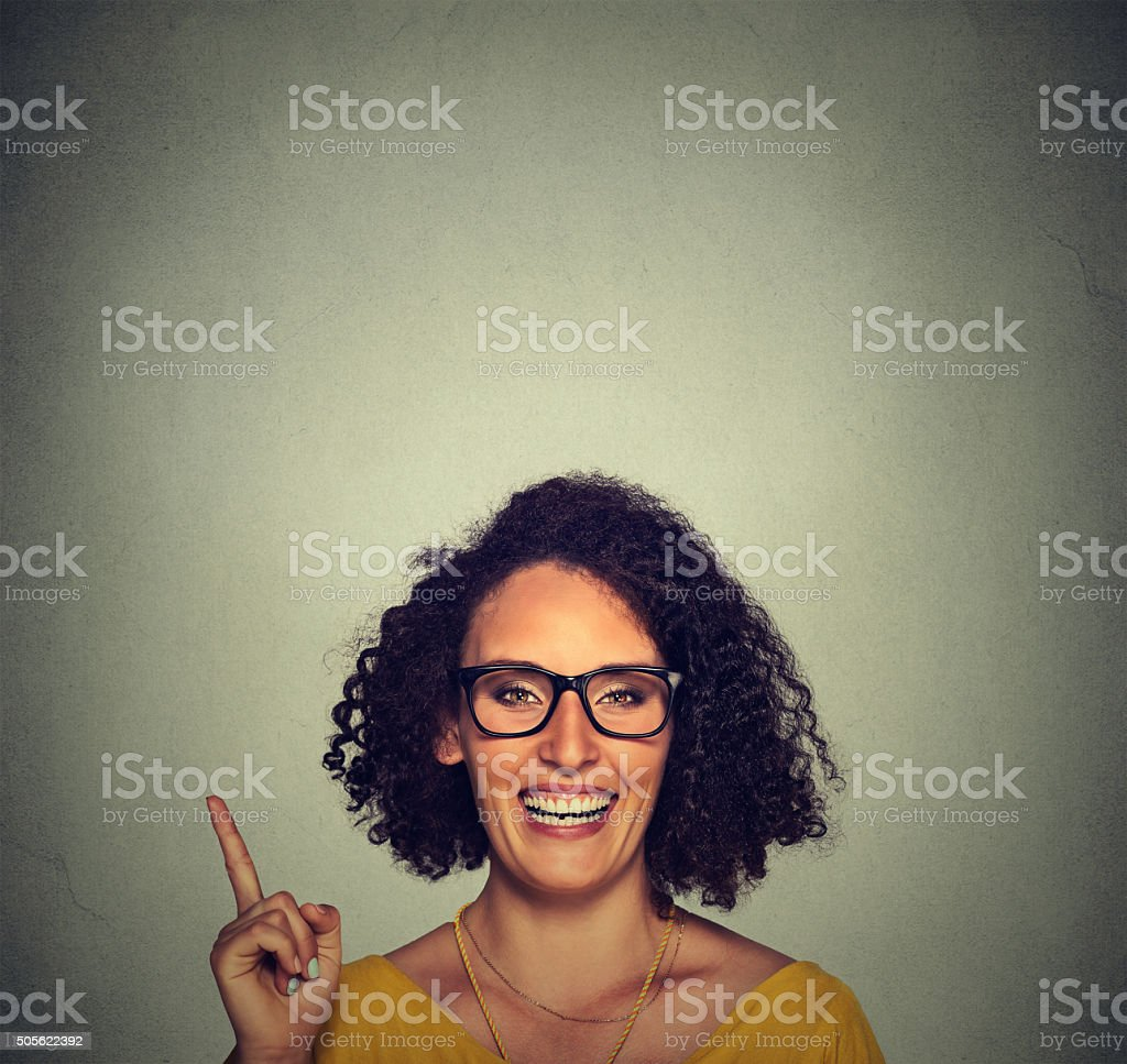 Happy woman in glasses pointing up with her finger stock photo