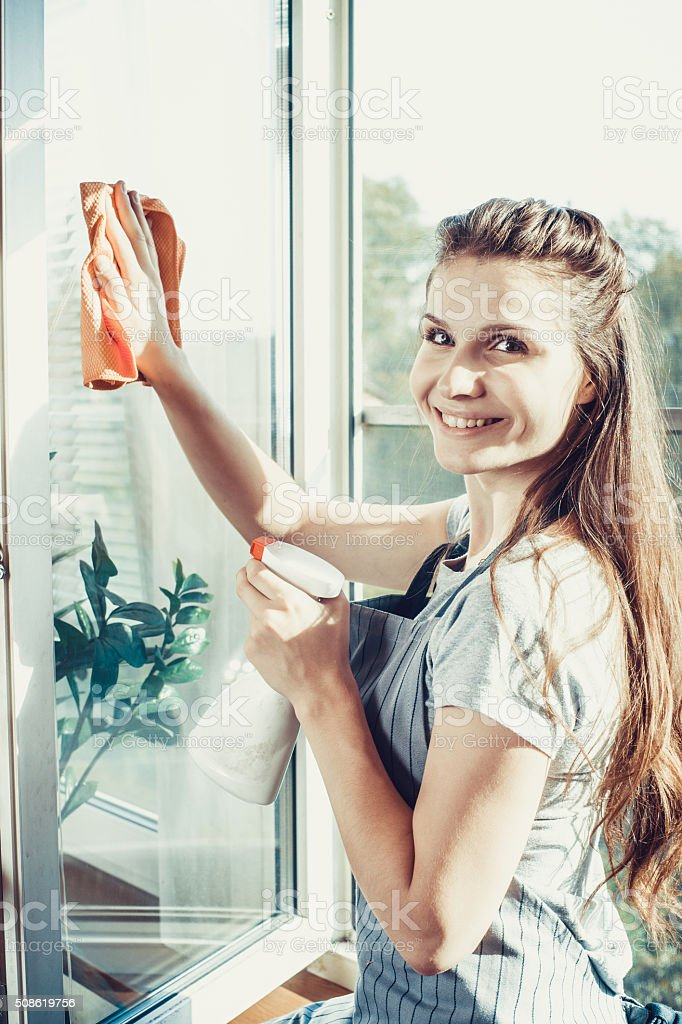 happy woman in gloves cleaning window stock photo