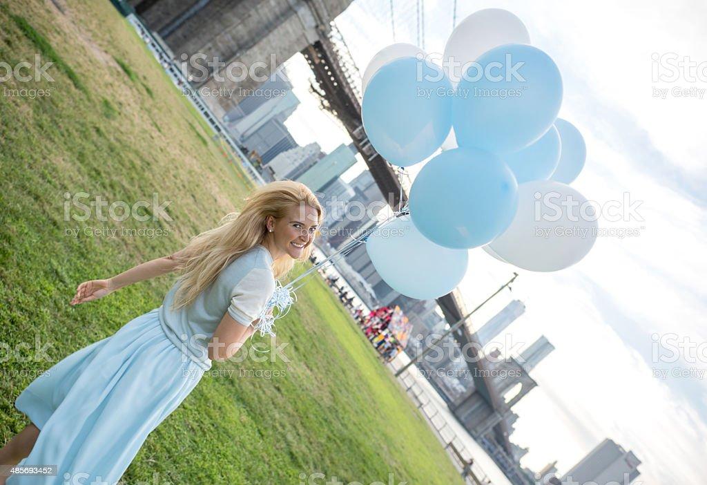 Happy woman in New York holding helium balloons stock photo