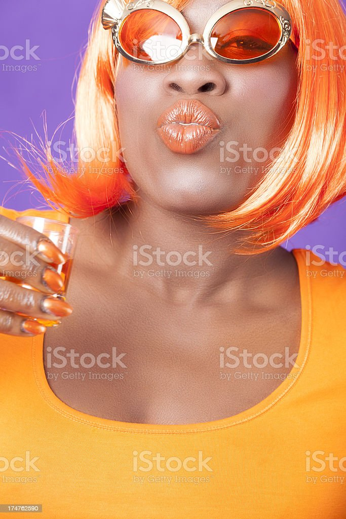 Happy woman in orange with wig drinking Oranjebitter stock photo
