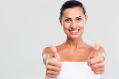 Happy woman in towel showing thumb up sign