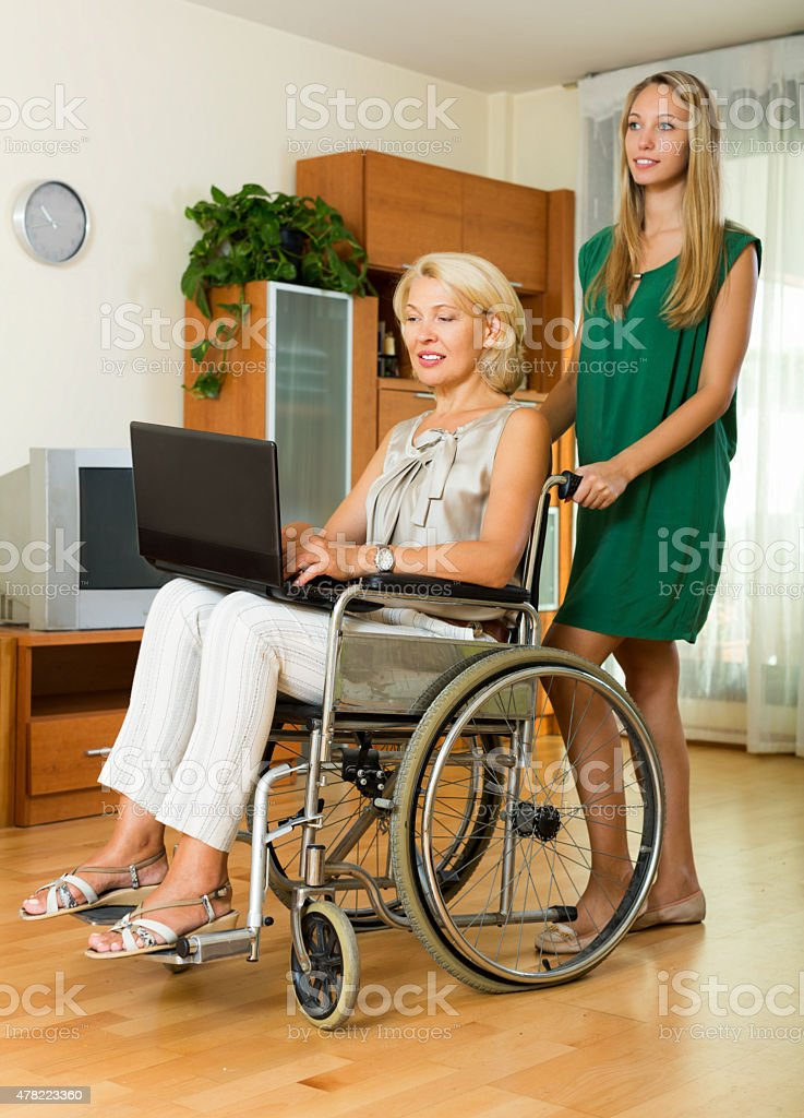 Happy woman in wheelchair  working on laptop stock photo