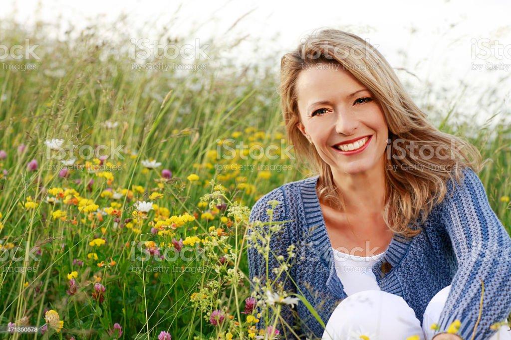 Happy woman in wild flower field stock photo