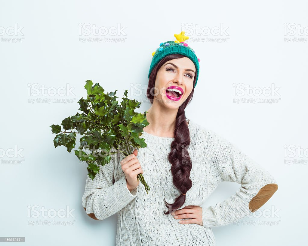 Happy woman in winter outfit holding a sprig of holly stock photo