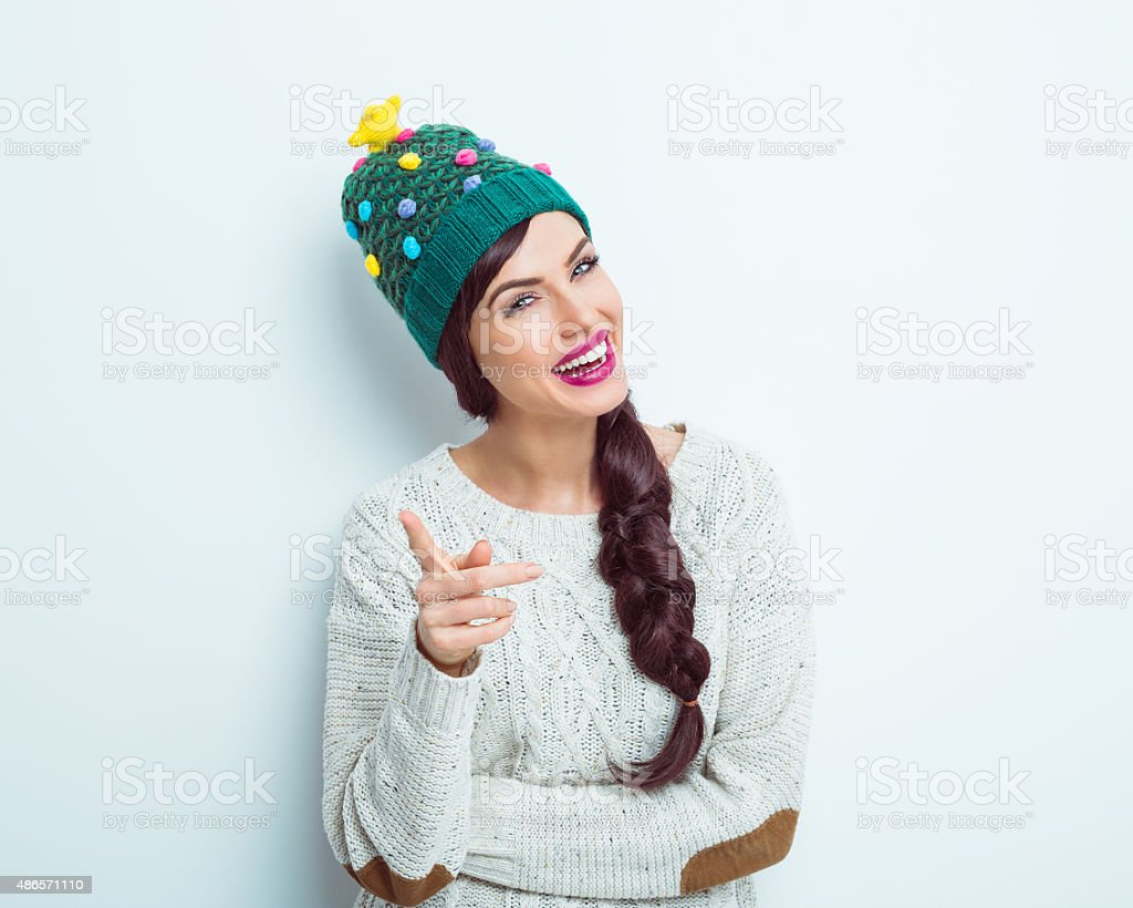 Happy woman in winter outfit pointing at camera stock photo
