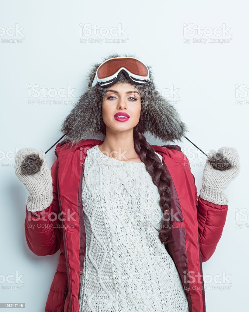 Happy woman in winter outfit - puffer jacket, fur hat stock photo