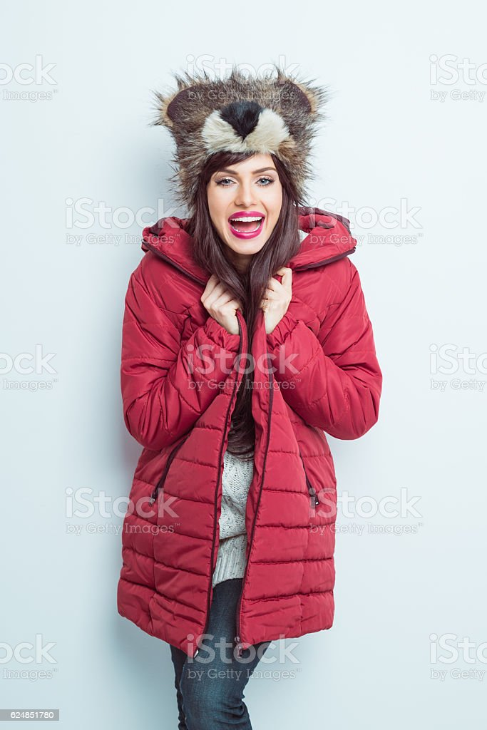 Happy woman in winter outfit, wearing bear head fur hat stock photo