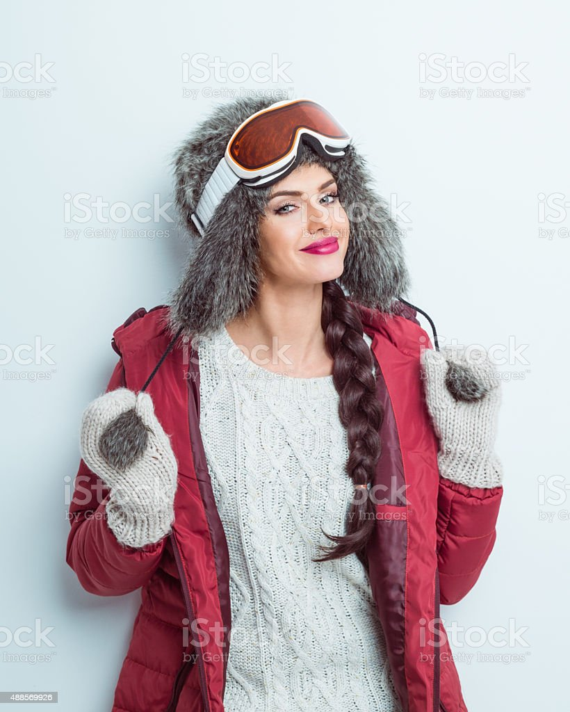 Happy woman in winter outfit, wearing fur cap and goggle stock photo