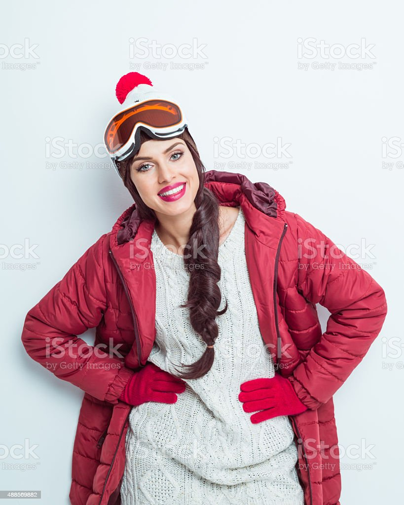 Happy woman in winter outfit, wearing woolen cap and goggle stock photo