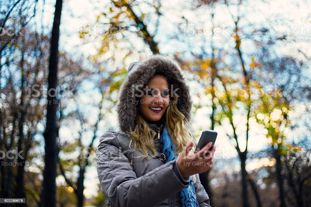 Happy woman in winter park talking mobile phone, sms. stock photo
